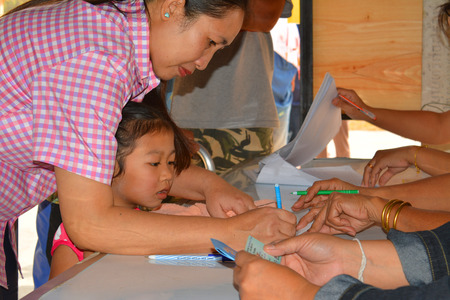 voting booth: MAHASARAKHAM - JANUARY 29 : A woman goes to vote for village headman election at Ban Nong Hin on January 29, 2015 in Muang, Mahasarakham, Thailand.