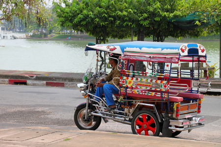 ROI-ET, MARCH 22 : Tricycle motor car driver is waiting for passenger at Palanchai swamp and public park on MARCH 22, 2015 in Roi-Et, Thailand.