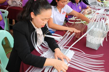 mahasarakham: MAHASARAKHAM - MARCH 9 : Group of women learn to weave plastic basket at Fix It Center public exhibition on March 9, 2015 in Mahasarakham, Thailand. Editorial