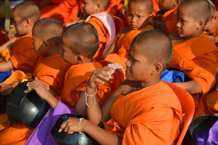 alms: PAYAKKAPHUMPHISAI - APRIL 13 : Buddhist novices are waiting for people to give food for alms on April 13, 2015 in Payakkaphumphisai, Mahasarakham, Thailand. This day is Songkran Day.