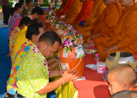 PAYAKKAPHUMPHISAI - APRIL 13 : People give offering for alms to Buddhist monks on April 13, 2015 in Payakkaphumphisai, Mahasarakham, Thailand. This day is Songkran Day.
