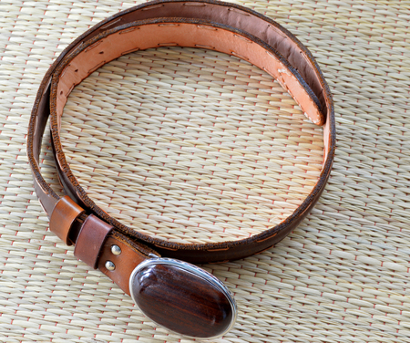 waistband: leather belt with Siamese Rosewood buckle on a mat Stock Photo