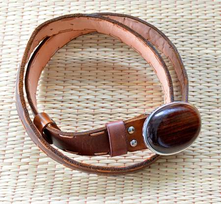 rosewood: leather belt with Siamese Rosewood buckle on a mat Stock Photo
