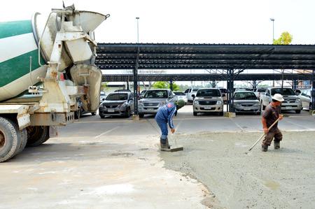 mahasarakham: MAHASARAKHAM - OCTOBER 8 : Masonry workers repair concrete parking floor at Sermthai complex on October 8, 2014 in Mahasarakham, Thailand. Editorial