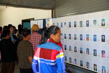 polling booth: PAYAKKAPHUMPHISAI  JUNE  28 : Villagers check candidate name for representative of farmers reconstruction and development fund on June 28 2015 in Payakkaphumphisai Mahasarakham Thailand.