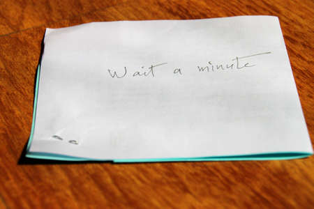 scarp:  wait a minute  handwritten on note paper on wooden floor Stock Photo