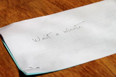 note paper:  wait a minute  handwritten on note paper on wooden floor Stock Photo