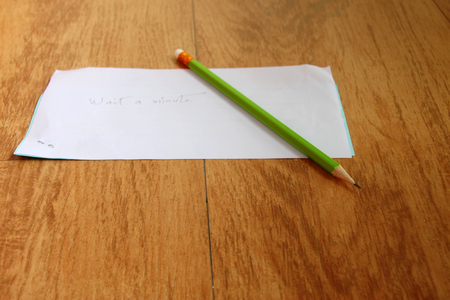scarp: green pencil and  wait a minute  handwritten on note paper on wooden floor Stock Photo