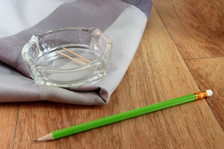 tela algodon: cenicero en tela de algod�n y un l�piz verde en el suelo de madera en la sala de Foto de archivo