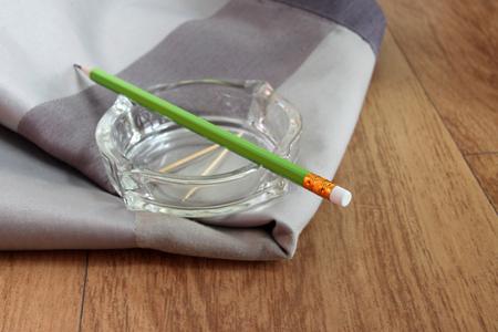 tela algodon: l�piz verde en el cenicero dispuesto sobre tela de algod�n en el suelo tabl�n Foto de archivo