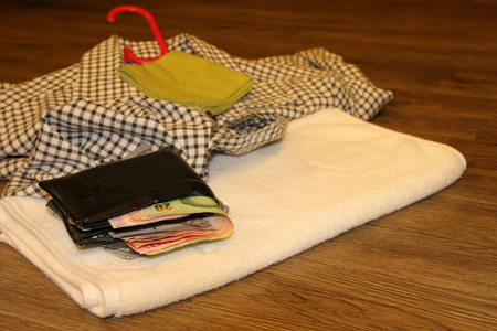 clotheshanger: money purse and towel on wooden floor in the morning light room