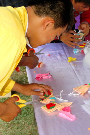 facilitator: MAHASARAKHAM - MARCH 9 : Service provider man is making clothes doll at Fix It Center public exhibition on March 9, 2015 in Mahasarakham, Thailand.