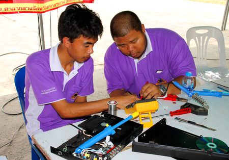 facilitator: MAHASARAKHAM - MARCH 9 : Service provider men are repairing electric appliances at Fix It Center public exhibition on March 9, 2015 in Mahasarakham, Thailand. Editorial