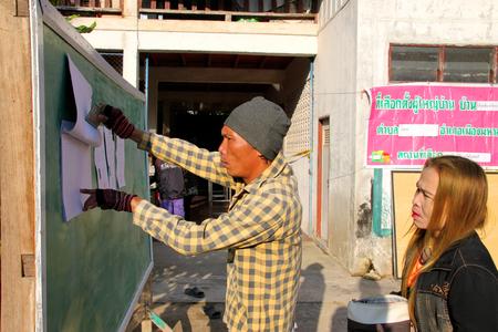 encuestando: Mahasarakham - 20 de enero: el elector está comprobando la lista de votantes calificados para la elección alcalde pedáneo en Wat Ban Chiang Hean lugar de votación el 20 de enero de 2015, de Muang, Mahasarakham, Tailandia. Editorial