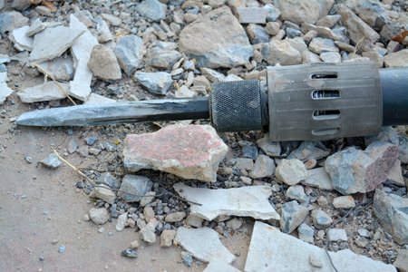 desertion: electric drill deserted on broken stone ground Stock Photo