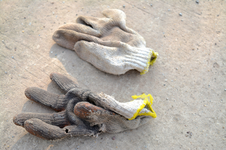 outworn: old worker gloves deserted on concrete ground Stock Photo