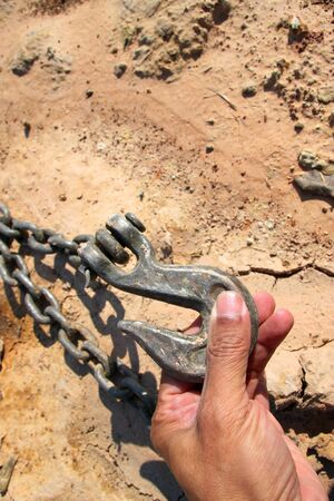 building a chain: metal hook and chain in building site Stock Photo