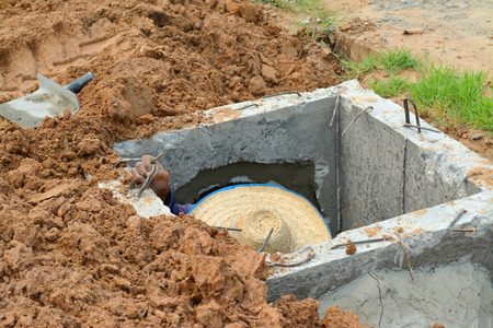dirtiness: man in cement pipe of sanitary sewer drainage system development
