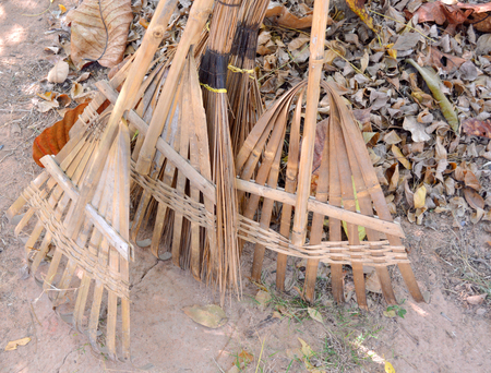 yard stick: old brooms and harrows on the ground Stock Photo