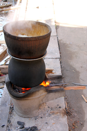stainless steel pot: sticky rice in earthenware steamer on boiled water in a stainless steel pot on a charcoal brazier stove, rice cooking