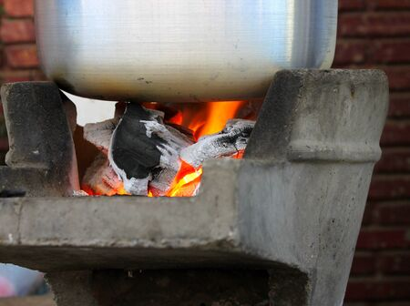 stainless steel pot: boiled water in a stainless steel pot on a charcoal brazier stove