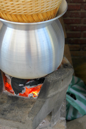 stainless steel pot: sticky rice cooking, boiled water in a stainless steel pot on a charcoal brazier stove Stock Photo