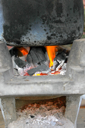 stainless steel pot: boiled water in a black stainless steel pot on a charcoal brazier stove