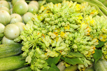 pile of cowslip creeper flowers and vegetables at Thai local market stall Stock Photo