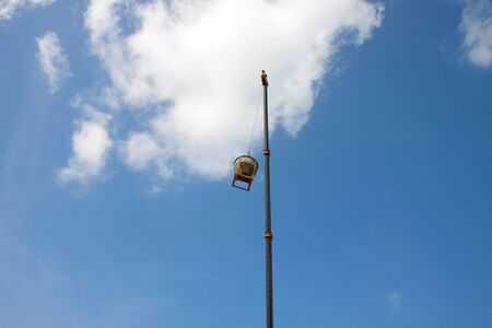 windlass: crane lifting mixed concrete container against blue sky at construction site Stock Photo
