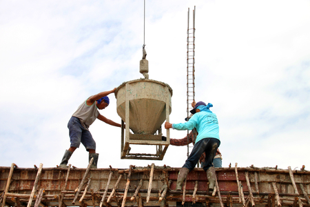 windlass: YANGSRISURAT - JULY 11 : Mixed concrete container bucket is sent by crane to workers at city hall building site on July 11, 2016 in Yangsrisurat, Mahasarakham, Thailand.