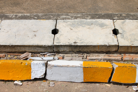 manhole and exemplary warning sign of white and yellow color on road Stock Photo