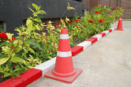 exemplary: traffic cone and exemplary warning sign of red and white color on road