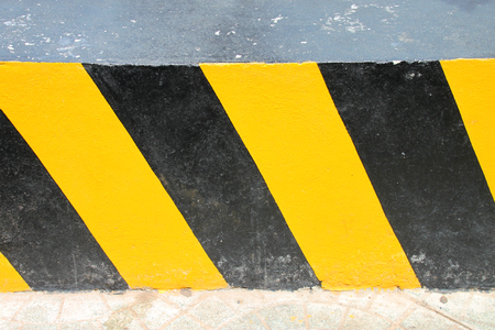 chunky: black and yellow slash linear pattern painted as warning sign and symbol on chunky and thick concrete
