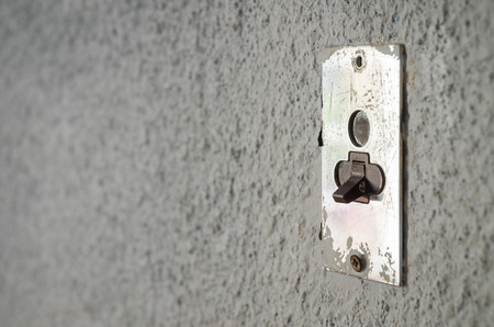 metal base: An old lightning electrical metal switch on gray wall  Metal base with plastic switch  Clean composition with copy space for text, words, etc  nobody in picture  empty
