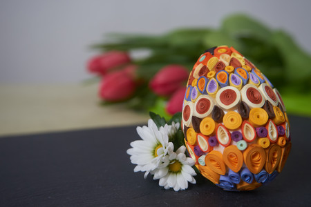 Easter egg decorated with the quilling technique on the gray surface near of red tulips. Easter decor, selective focus.