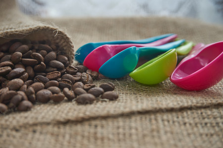 Dark roasted coffee beans on hessian or burlap with colorful plastic kitchen measuring spoons in a shallow dof low angle view