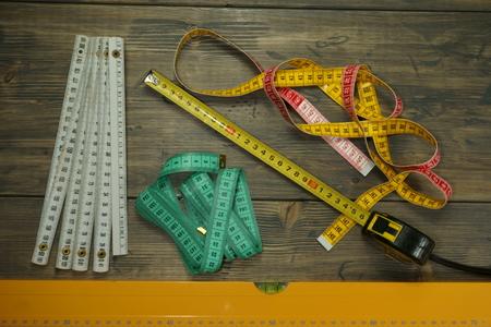 Sélection de différents outils de mesure sur fond de bois rustique avec niveau à bulle gradué et mètre ruban assorti Banque d'images