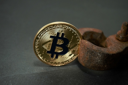 Close up of old rusty vintage nippers holds golden bitcoin Cryptocurrency under pressure risk mining conceptual image with copy space