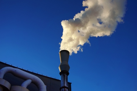 White smoke coming out of metal industrial chimney with blue sky background. Air pollution, greenhouse effect and global warming problem concept.