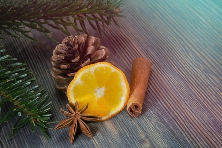 Piece of lemon, cinnamon and badian star anise next to pine branch and conifer cone, sitting on wooden table surface background with copy space. Mulled wine recipe concept Imagens