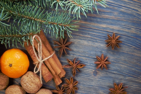 Christmas layout concept on wooden background with cinnamon and badian star spices, pine foliage, mandarine and fresh whole nuts in their shells 免版税图像