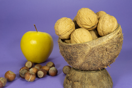 Whole common walnuts with shells in natural coconut shell cup, pile of whole hazelnuts and yellow apple on purple background