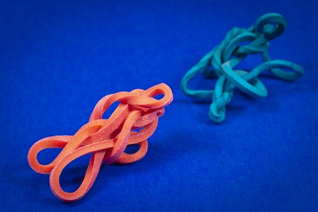 Old blue cracked and new red twisted rubber bands centered on blue background with copy space Stock Photo
