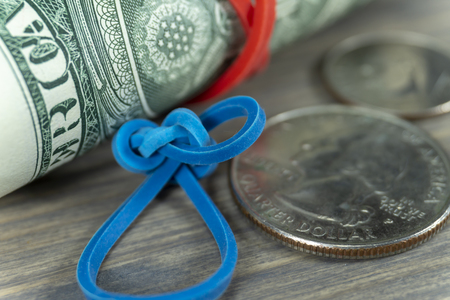 Roll of USD bills with blue rubber band and dollar coins in a close up view on wood conceptual of trade, business, investment, savings, retirement, finance and money Banco de Imagens