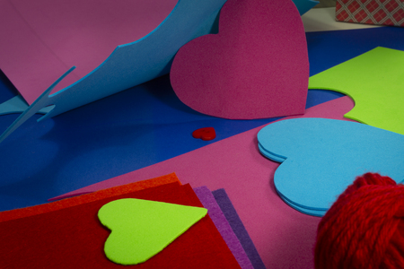 Colorful balls or red yarn and cardboard with heart shaped cut outs for handicrafts or scrapbooking. Love and relationship Valentines Day and color trends concept