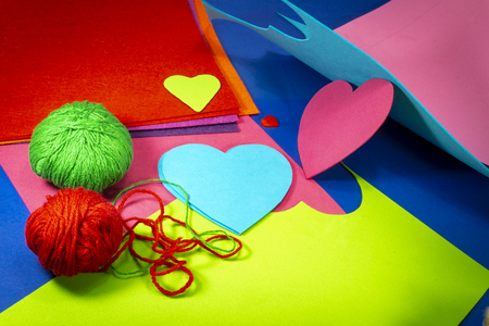 Colorful balls or red and green yarn and cardboard with heart shaped cut outs for handicrafts or scrapbooking. Love and relationship Valentines Day and color trends concept