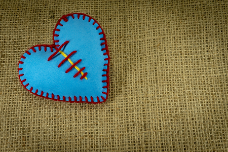 Valentine Day template, one handmade blue foam sheet stitched toy heart on jute canvas, close up, high angle view. Love, relationship, Valentines Day, broken heart and gay love concept
