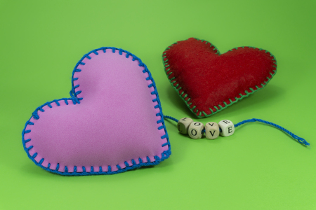 Hand stitched textile hearts with word Love on blocks threaded on strings on green chromakey background for romantic relationship, Valentines Day, broken heart and concept Stock Photo