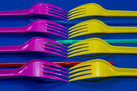 Yellow and pink cutlery plastic forks and straws arranged on blue background. Color trends and plastic waste problem concept