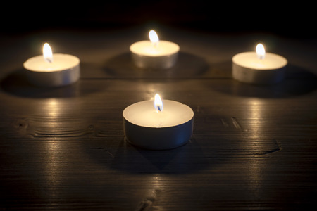 Four tea candles in the dark with shallow depth of focus on a wooden surface